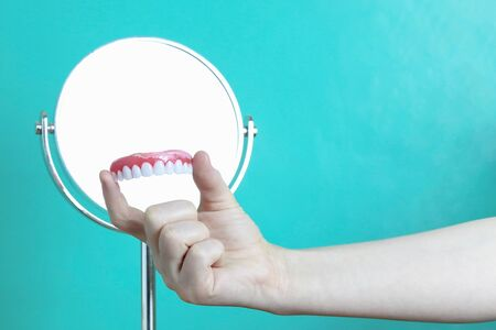 Denture in hand and round mirror. Copy space - concept of dentistry, dental treatment Archivio Fotografico