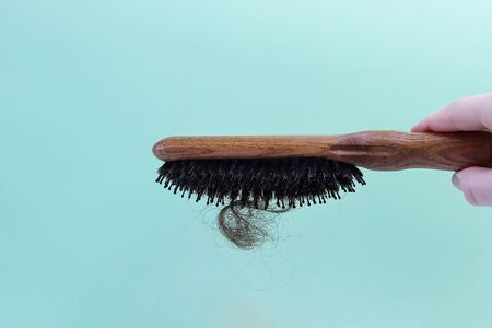 Fallen hair and a wooden comb. Copy space - concept of health problems, treatment, baldness, serious illness