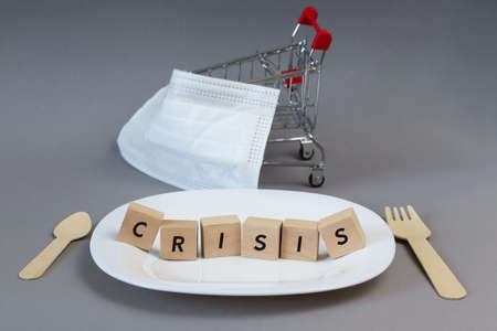 The word crisis made from cubes on an empty white plate. Defocused medical mask. Copy space - concept of economic problems, hunger, symbol, food, consequences of coronavirus. Imagens