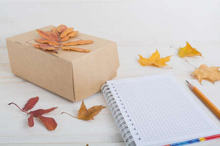 yellow notepad:  craft paper box, notebook, pencil decorate autumn leaves. autumn business concept. Stock Photo