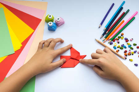 freshwater bird: Childrens hands do origami  bird from red paper. Working place is decorated with leaves of color paper, scissors, colored wood ladybugs and pencils.