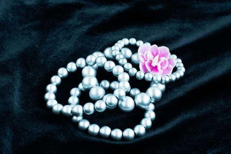 faux: bracciali perle finte su un velluto nero Archivio Fotografico