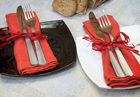forks and knives with red napkin lying on plates photo