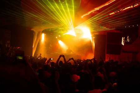 aplaudiendo: Noche de club de dj fiesta personas disfrutan de música bailando sonido con luz de colores con máquina de humo y luces muestran. Manos arriba en la tierra.