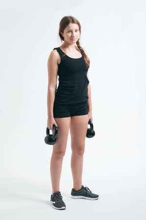 teenage girl during the squat with the kettlebells over the white background Фото со стока