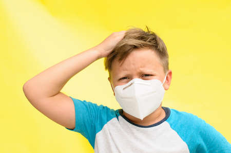 Horizontal portrait of an unhappy boy with the disposable mask on the face holding the head with one hand over the yellow background