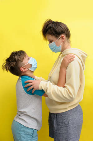 Vertical photo of a boy and teenaged girl in disposal masks embracing each other and looking at each other over the yellow background