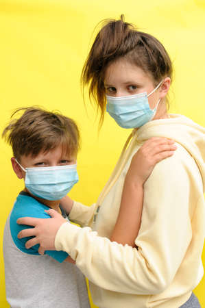 the portrait of a boy and teenaged girl in disposal masks embracing each other and looking at camera over the yellow background