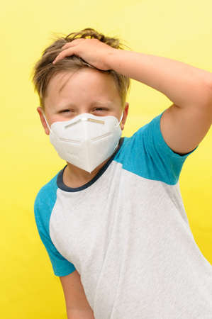 A vertical portrait of a boy with the disposable mask on the face looking into the the camera over the yellow background