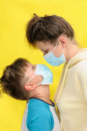 Closeup of a boy and teenaged girl in disposal masks embracing each other and looking at each other over the yellow background