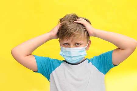 horizontal photo of a sad boy with the disposable mask on the face holding his head with the arms and looking into the camera over the yellow background 免版税图像