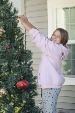 a happy teen girl in a pink hoodie decorating outdoor christmas tree