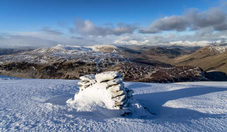 scotish: pile of stones on the top of scotish mountain in winter