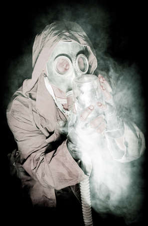 gasmask: men in the gas mask on the black background surrounded by smoke and breathing with green plant in the pot witch holds in his hands, survival soldier after apocalypse.