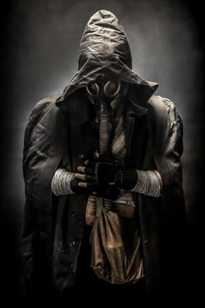 gasmask: man in the gas mask in the hood, on the black background surrounded by smoke, with hands on the chest, survival soldier after apocalypse. Stock Photo