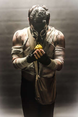 gasmask: Man in the gas mask, on the black background surrounded by smoke, looking at the pear in his hands, survival soldier after apocalypse.