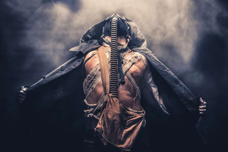 gasmask: man in the gas mask in the hood, on the black background surrounded by smoke,, survival soldier after apocalypse.