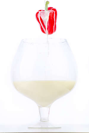 Red peppers hanging on a hook over a huge glass of milk on a white background. On paprika pouring milk in a thin stream