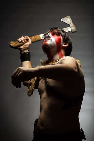brandishing: studio portrait of man in war paint, with an ax in his hand, a warrior brandishing an ax up furiously, indian.