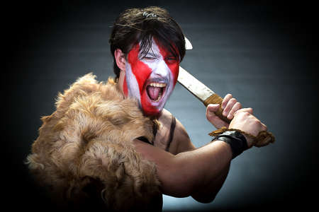 brandishing: Portrait of man in war paint, with an ax in his hands, a warrior brandishing an ax furiously screaming, barbarian of ancient times, Viking and savage. Stock Photo