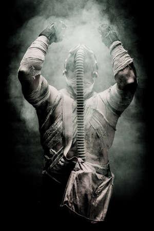 les hommes bandés dans le masque à gaz sur le fond noir entouré par la fumée et en regardant le ciel, la survie soldat après l'apocalypse.