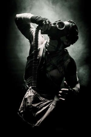 gasmask: bandaged men in the gas mask on the black background surrounded by smoke and looking at the sky, survival soldier after apocalypse.