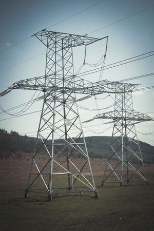 megawatts: vintage high voltage electric power lines on pylons, power transmission tower Stock Photo