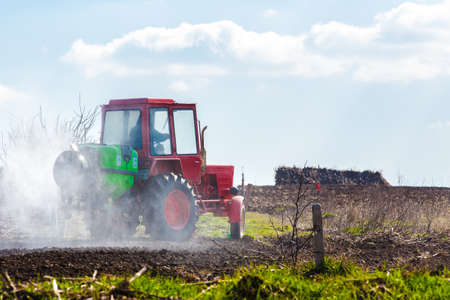 furrow: red tractor in a field waters garden, background