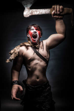 brandishing: Painted image of man in war paint, with an ax in his hand, a warrior brandishing an ax furiously screaming, barbarian of ancient times, Viking and savage. Stock Photo