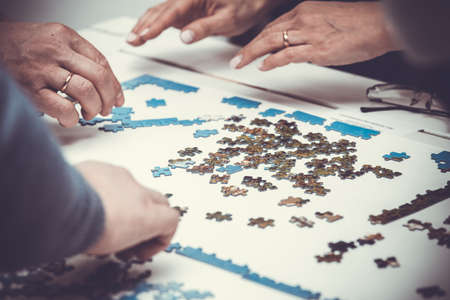 difficult lives: family hands solving jigsaw puzzle at home