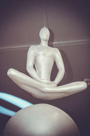 karmic: Mannequin in a lotus position soars above the ball soars