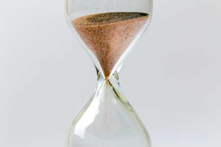 Sand flowing through an hourglass concept for time running out, background Stock Photo
