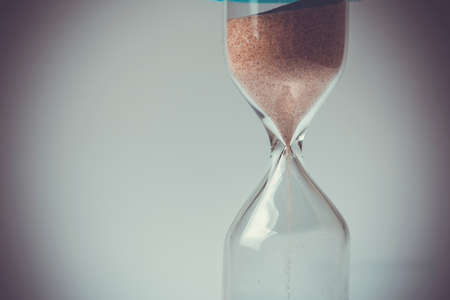 trickling: Sand flowing through an hourglass concept for time running out, background