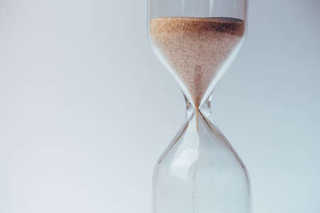 beat the clock: Sand flowing through an hourglass concept for time running out, background