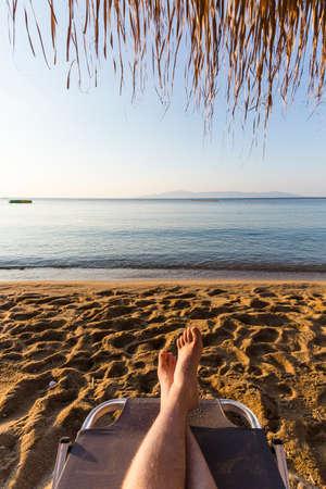 pair of male legs on sun lounger on the beach at sunrise Stock Photo