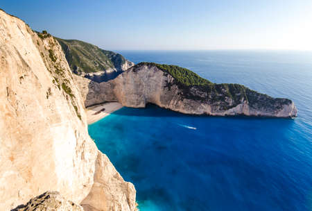 swimm: Navagio beach with shipwreck and motor boat on Zakynthos island in Greece, background