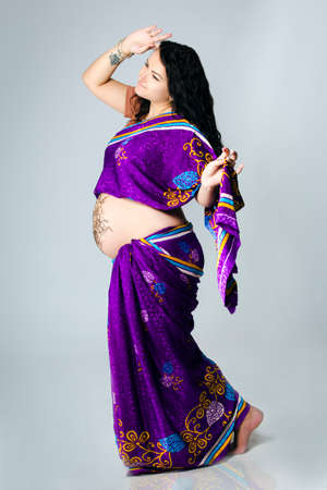 bracelet tattoo: studio portrait of a pregnant woman in Indian sari, a pregnant belly painted with henna