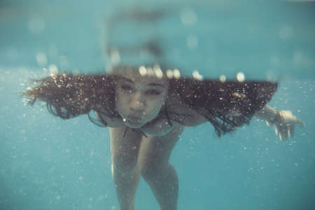 swim goggles: blur or defocus image of young woman swimming undewater in the sea. Young female swimmer with swim goggles at holiday resort. Stock Photo