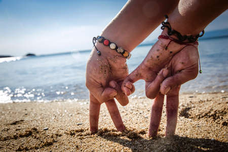 conceptual picture - two hands in the form of couple, walking on the beach at sunrise. personalized hands standing on two fingers symbolizing the people.