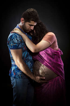 tenderly: Photo pregnant athletic couple on a black background. Man tenderly embracing his pregnant wife Stock Photo