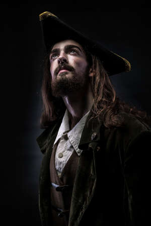 Portrait of a medieval bearded pirate thoughtfully looking up on a black background.