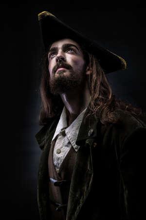 Portret van een middeleeuwse bebaarde piraat die zorgvuldig omhoog op een zwarte achtergrond kijkt.