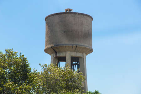 municipal utilities: photo of old concrete water tower on sky background, Greece