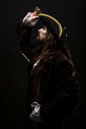 Portret van een middeleeuwse bebaarde piraat op zwarte achtergrond. Stockfoto