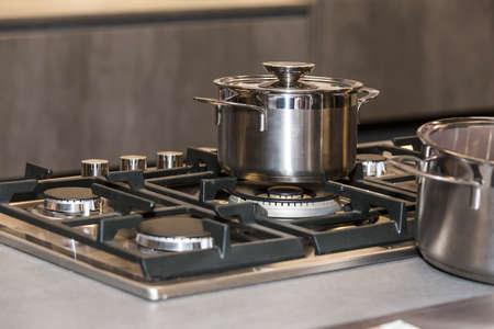 eating utensil: photo of shiny metal pan on a gas stove, shallow DOF focus on pan