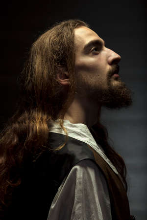 Personification of Jesus Christ, man with long hair and beard, peacefully looking up to the light