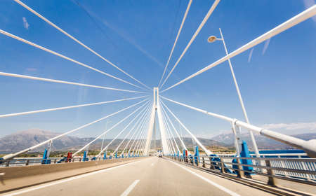 road to suspension bridge crossing Corinth Gulf strait, Greece