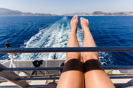 sexy young woman legs relaxing on cruise ship travel holiday.