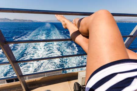 pernas de mulher jovem sexy relaxantes no navio de cruzeiro viajam de férias.