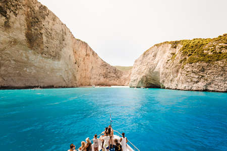 swimm: 10 July 2016 Amazing landscape of Navagio beach with shipwreck on Zakynthos island, cruise ship with people on deck, approaching to the bay. Greece.